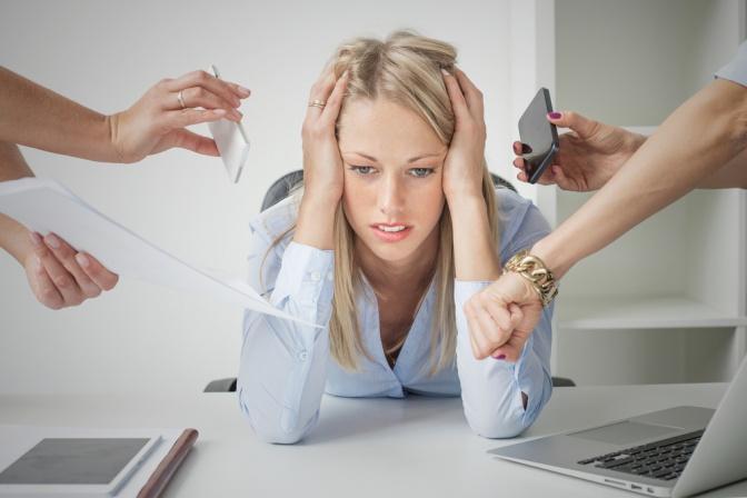 Eine Frau sitzt bei einem Schreibtisch und stützt sich auf Ihre Hände, viele Hände reichen zu ihr