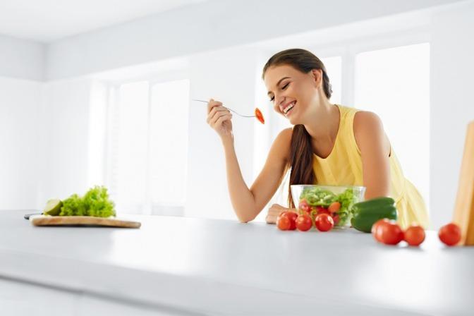 Eine Frau sitzt beim Tisch und isst gesund