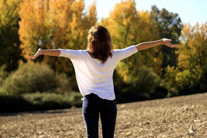 Eine Frau streckt frei die Hände zur Seite