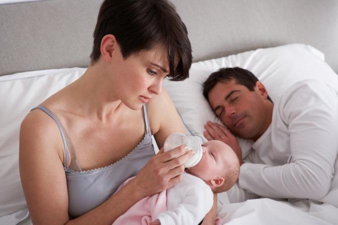 Eine Frau füttert ihr Baby mit der Flasche, der Mann schläft daneben