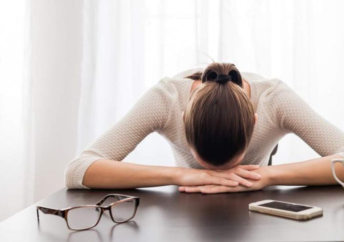 Gestresste Frau liegt mit dem Kopf auf dem Tisch