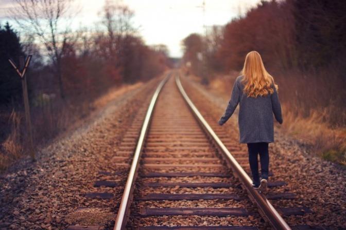 Eine Frau balanciert auf Gleisen