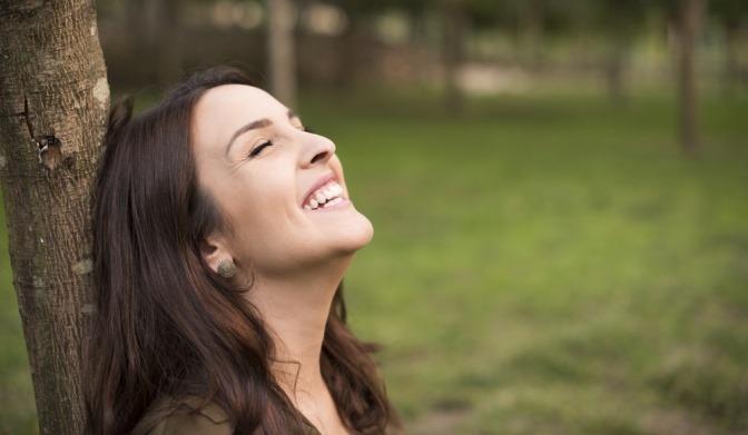 glückliche Frau lehnt an einem Baumstamm