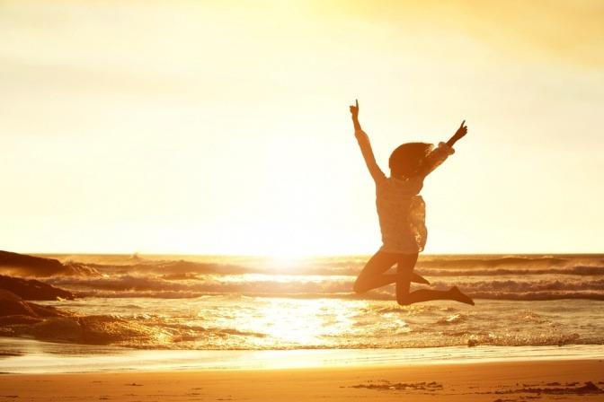Silhouette einer Frau, die begeistert in die Luft springt