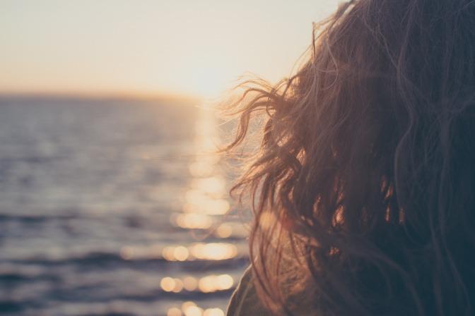 Eine Frau mit langen Haaren sitzt am Meer