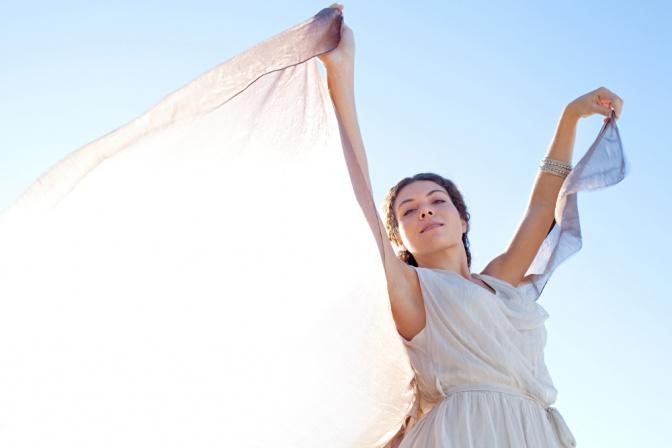 Eine Frau hält ihre Arme in die Höhe und sieht zufrieden aus