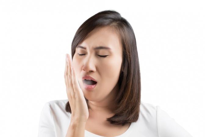 Eine Frau hat Mundgeruch