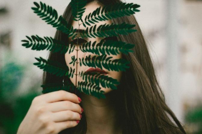 Eine attraktive Frau versteckt ihr Gesicht hinter einem Blatt