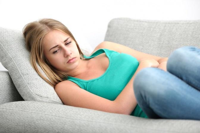 Eine Frau hat sich vor Übelkeit auf der Couch geparkt