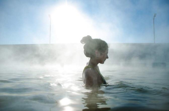 Eine Frau badet in einem beheizten Freischwimmbecken
