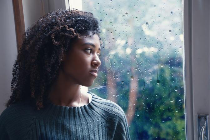 Eine Frau schaut aus dem Fenster und kann nicht weinen