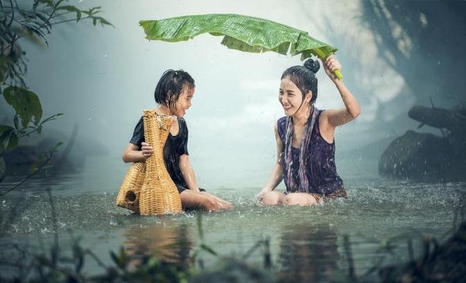 Eine Frau und ein Kind mit gutem Immunsystem sitzen im Wasser