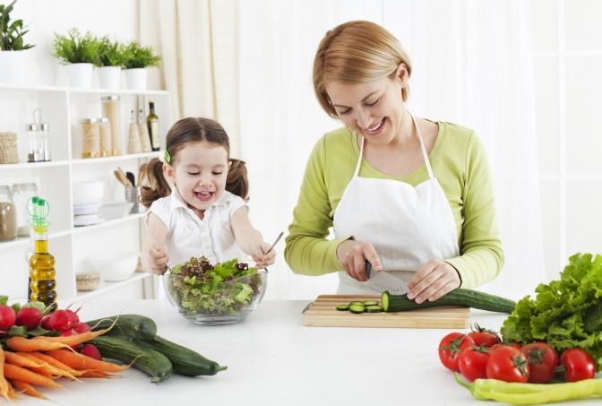 Eine Frau bereitet mit einem Kind eine Mahlzeit vor um vegetarisch essen zu können