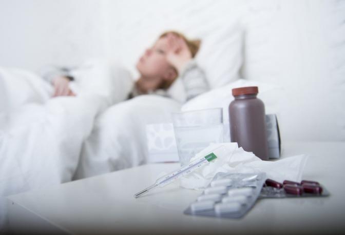 Eine Frau liegt im Bett, vor ihr stehen Medikamente
