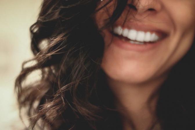 Eine Frau mit dunklem lockigem Haar und weißen Zähnen lächelt