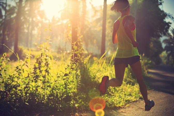 Eine sportlich gekleidete Frau läuft durch den Wald