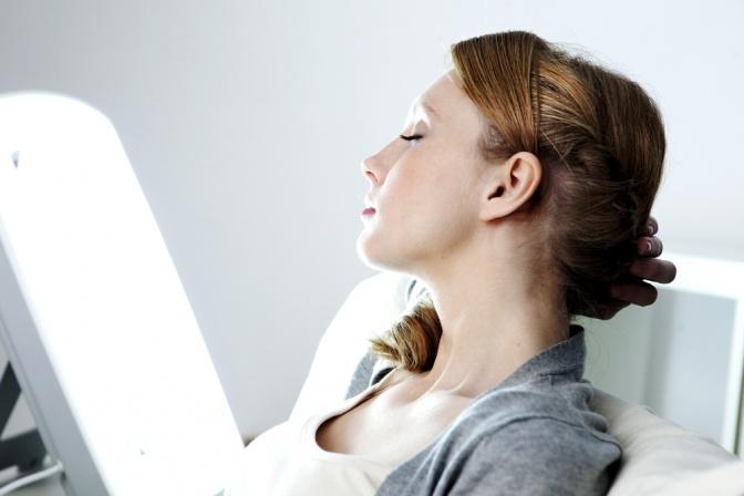 Eine Frau sitzt vor einer Lampe zur Lichttherapie gegen Winterdepression