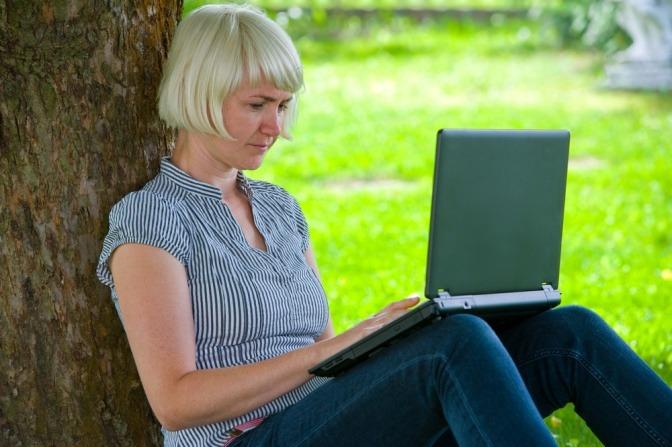 Eine Frau recherchiert im Internet Tipps zu nachhaltigem Bauen und Wohnen