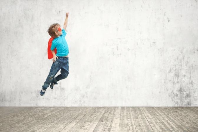 Ein Kind springt im Superhelden-Kostüm in die Luft