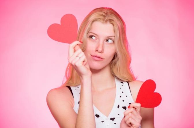 Eine Frau hält rote Valentinsherzen in der Hand und wirkt nachdenklich.