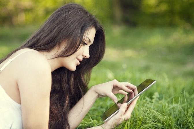 Eine Frau liegt in der Wiese und liest am Ipad