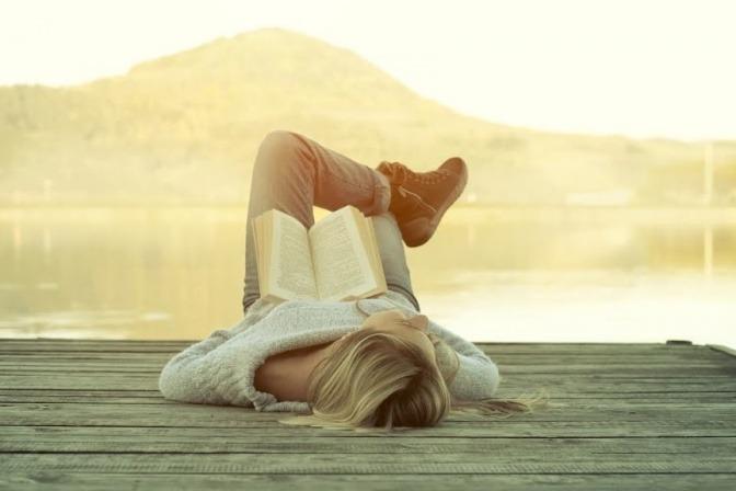 Eine Frau liegt auf einem Steg und liest ein Buch