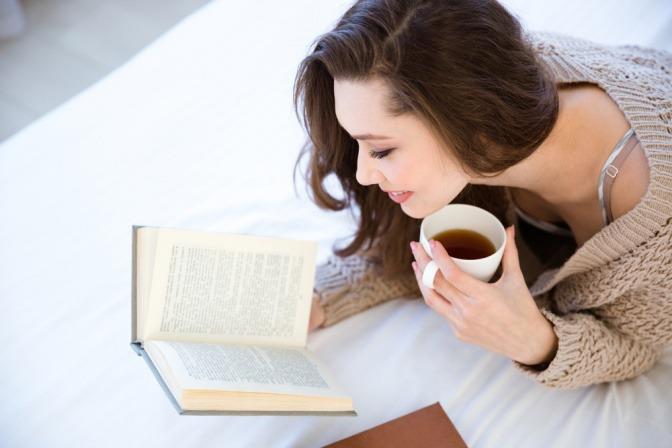 Eine Frau liest in einem Buch und hält eine Tasse