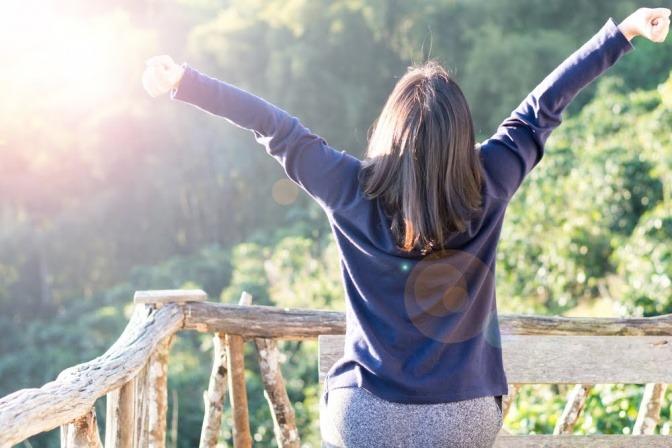 Eine Frau streckt die Arme losgelassen und frei gen Himmel