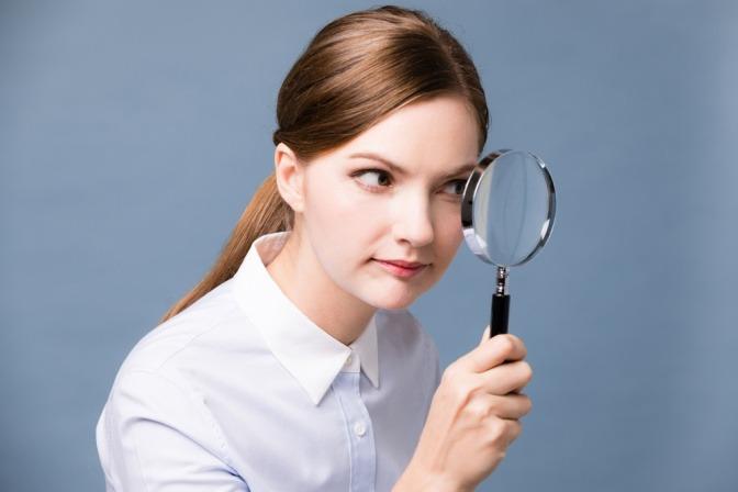 Eine junge Frau nimmt mit einer Lupe etwas in Augenschein.