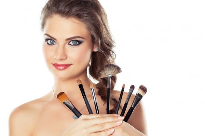Eine Frau mit verschiedenen Make up Pinseln