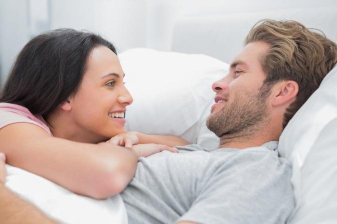 Eine Frau und ein Mann reden im Bett