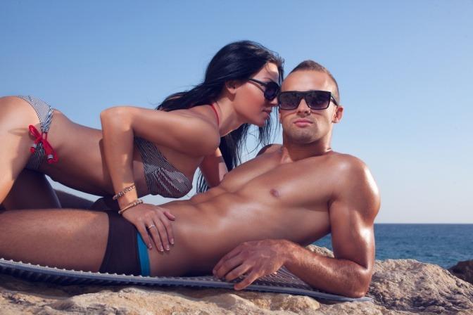 Eine Frau will am Strand einen Mann zum Sex im Urlaub verführen