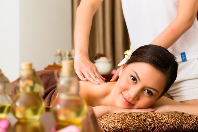Eine Frau liegt bei einer Lomi Lomi Massage, Öle stehen daneben