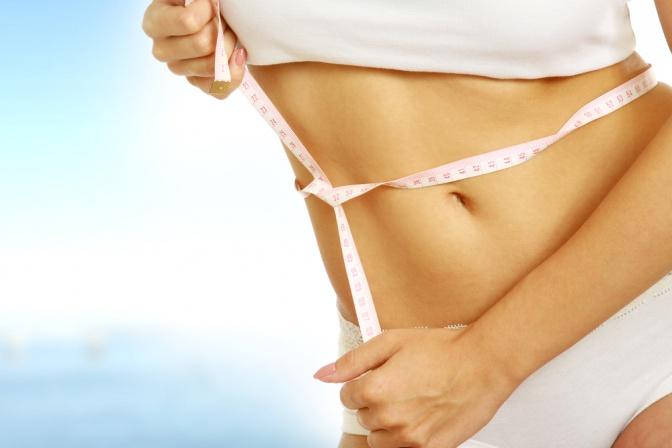 Der Bauch einer Frau ist abgebildet. Um ihn herum ist ein Maßband. Der Bauch ist sehr flach und einige Muskeln sind zu sehen. Die Frau trägt einen weißen Slip und ein weißes Top.