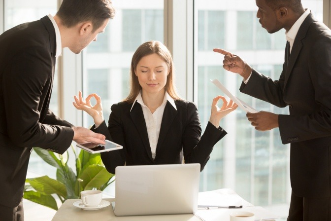Eine Frau meditiert im Büro während zwei Männer miteinander diskutieren