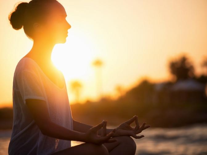 Eine Frau meditiert bei Sonnenuntergang