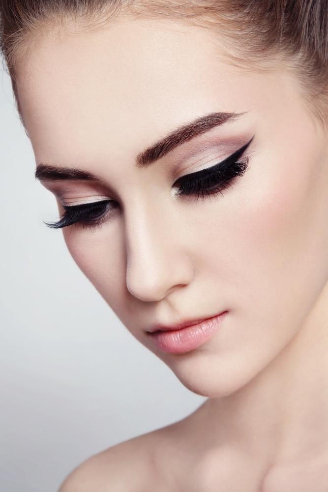 Eine Frau trägt einen dicken Eyeliner-Strich auf ihrem oberen Augenlid