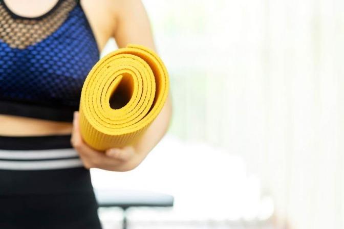 Eine Frau im Sportoutfit hält eine gelbe Fitnessmatt in der Hand