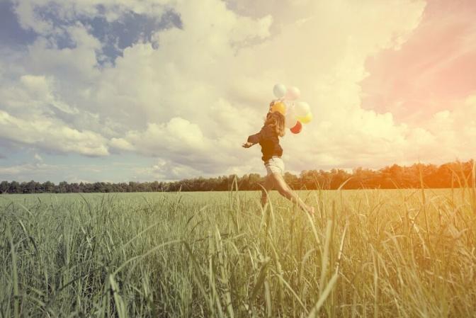 Eine Frau geht über ein Feld und hält Luftballone in der Hand