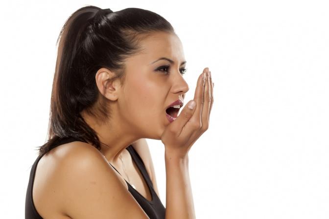 Eine Frau hält ihre Hand vor den Mund und hat Mundgeruch