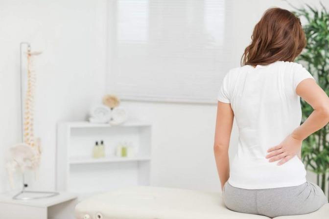 Frau mit Rückenbeschwerden beim Arzt.