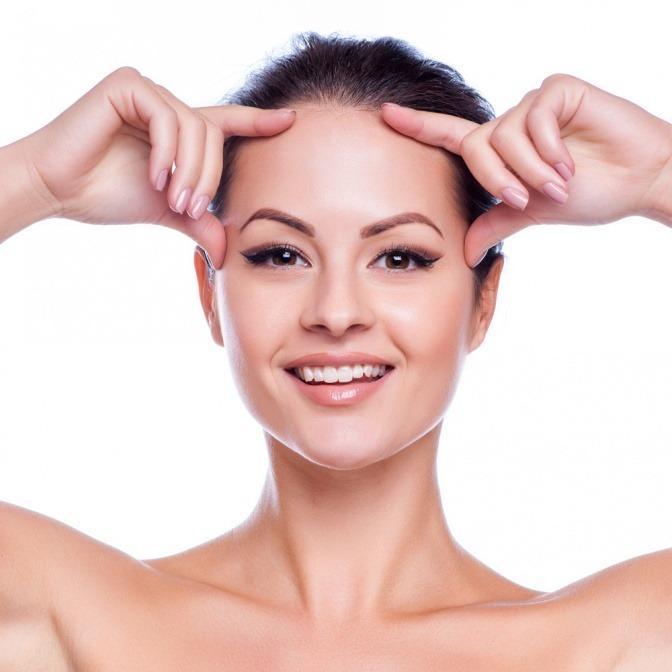 Eine Frau ohne Falten hält die Hände auf die Stirn