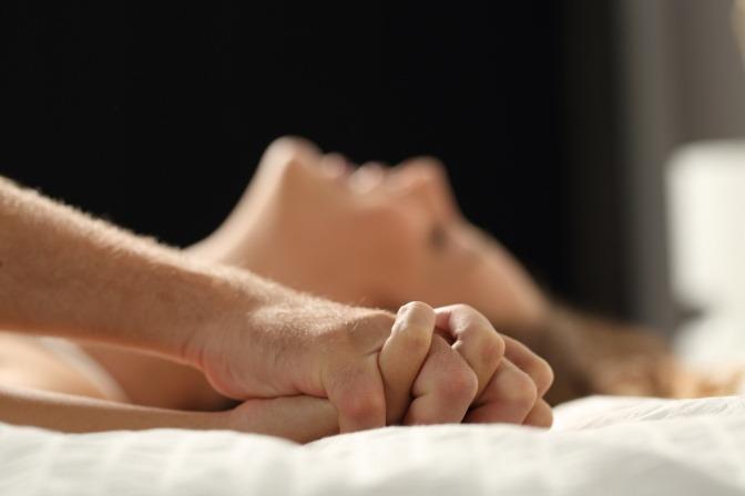 Eine Frau liegt erregt im Bett
