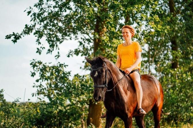 Eine Frau reitet ohne Sattel auf einem schwarzen Pferd