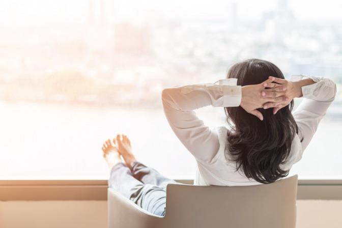 Eine Frau legt die Füße hoch und schaut aus dem Fenster