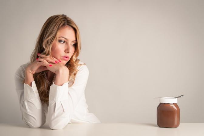 Eine Frau schaut auf ein Glas mit Schokoladecreme