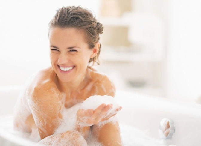 Eine glückliche Frau sitzt in der Badewanne