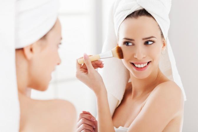 Eine Frau blickt in den Spiegelt, lächelt und trägt sich mit einem Pinsel Puder auf