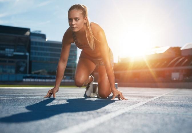 Eine Frau ist auf einer Laufbahn und bereitet sich auf einen Sprint vor