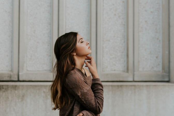 Eine Frau steht vor einer hellen Mauer und atmet durch